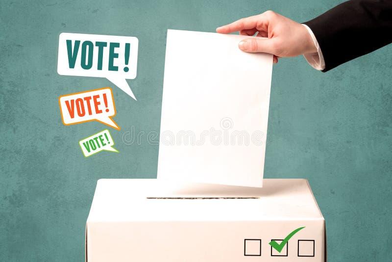 Colocando um deslizamento de votação em uma urna de voto foto de stock