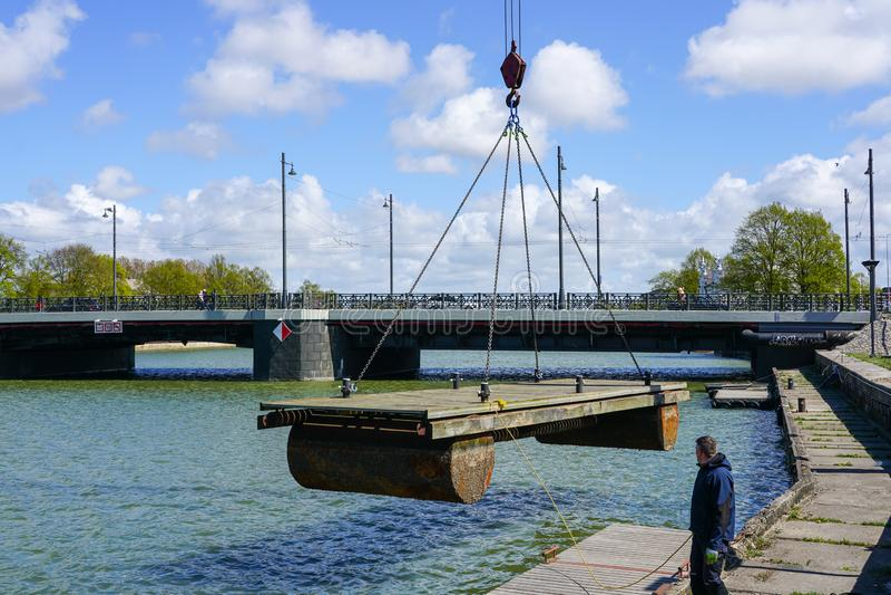 Colocando um pontão de flutuação do porto na água com a ajuda de um guindaste foto de stock