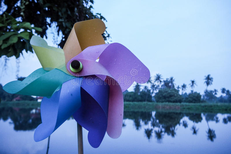 Coloeful wind turbine /pinwheel toy with river background landscape. Pinwheel / wind turbine toy royalty free stock images