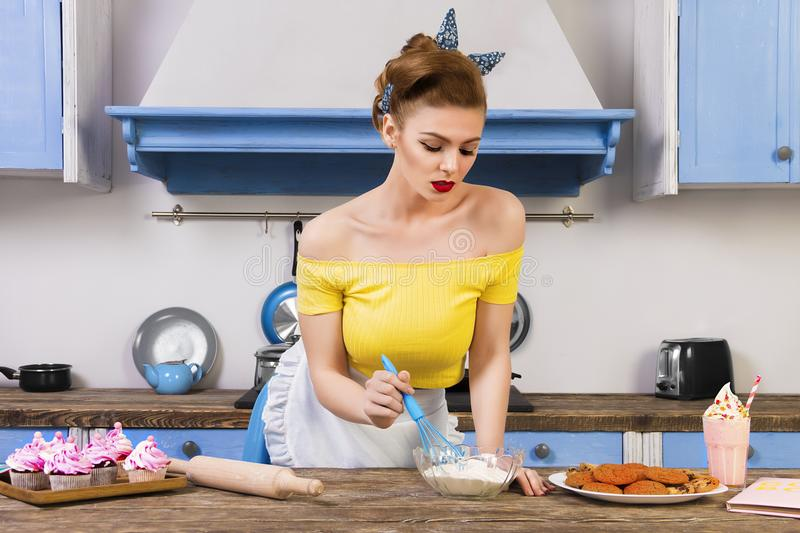 Retro pin up girl housewife in the kitchen. Coloful retro / pin up girl woman female / housewife wearing colorful top, skirt and white apron cooking in the stock photo