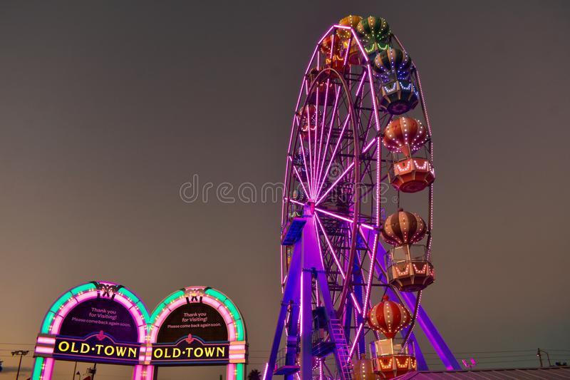 Colofur arches and Ferris Wheel on sunset background at Old Town Kissimmee in 192 Highway area. royalty free stock photos