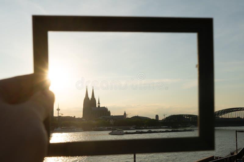 Cologne cityscape och landskap och horisont under solnedgångho en bildram royaltyfri fotografi