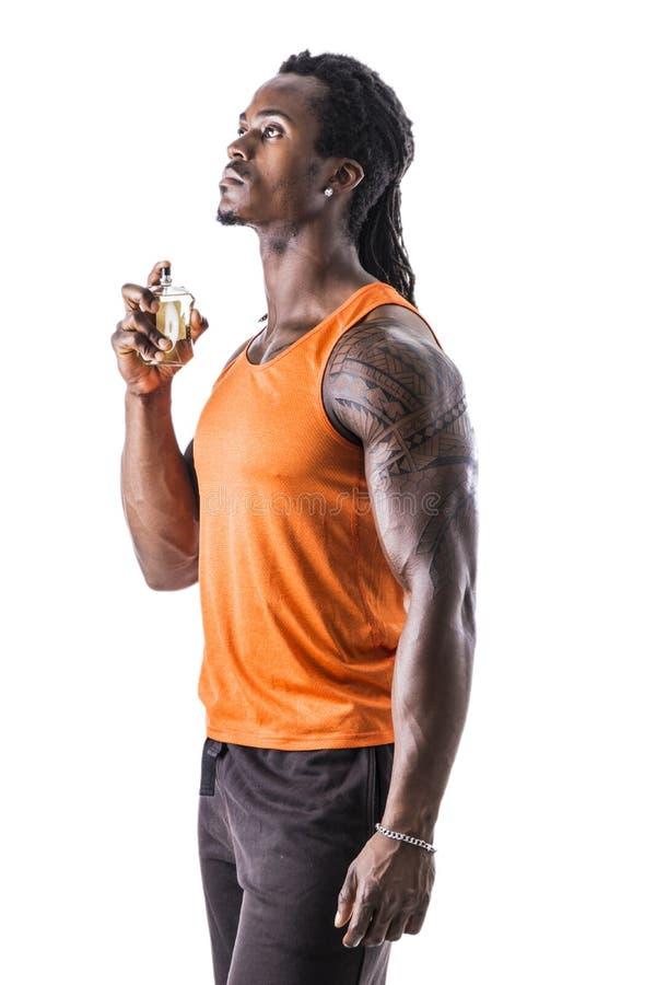 Cologne de rociadura del modelo masculino muscular negro fotografía de archivo