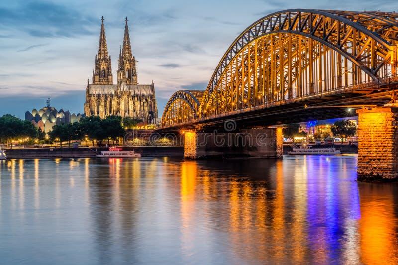 Cologne domkyrka och Hohenzollern bro på natten, Tyskland royaltyfri fotografi