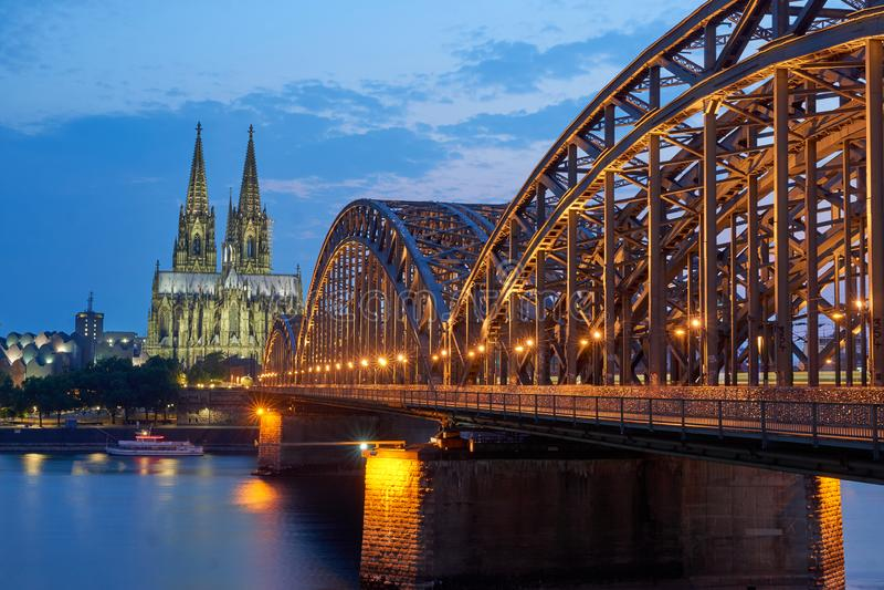 Cologne domkyrka och hohenzollern bro på solnedgången royaltyfria bilder
