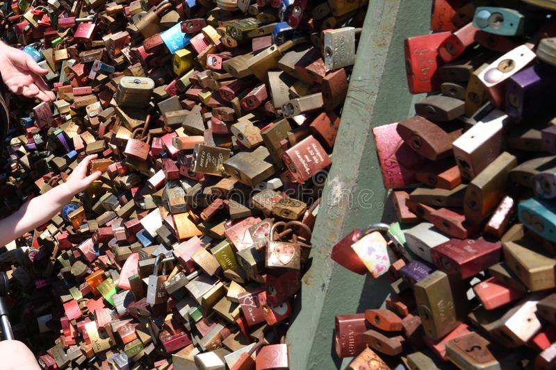 Cologne, Germany - July 16 2018: Baby`s hand reaching and searching for parent`s love lock on bridge stock images
