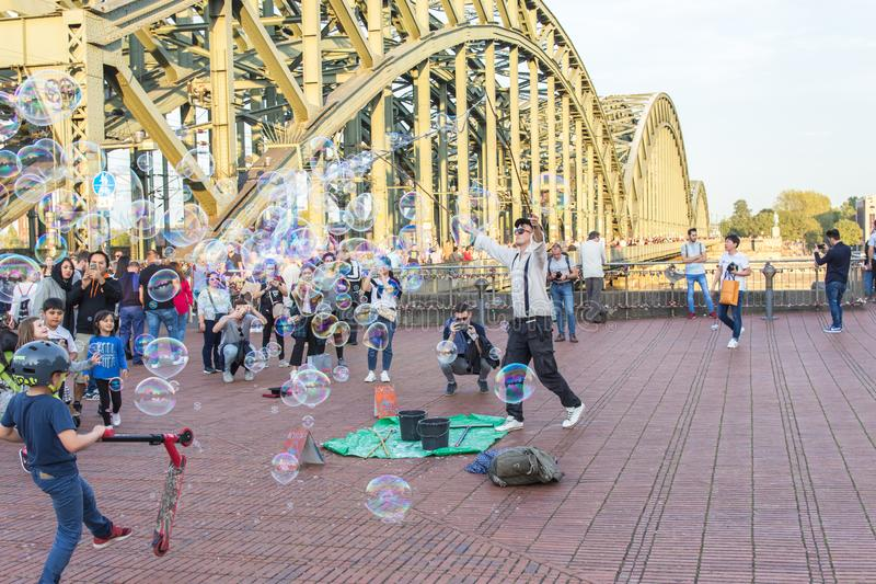 COLOGNE, GERMANY- OCTOBER 06, 2018: Walking tourists watching a guy blowing bubbles. royalty free stock images
