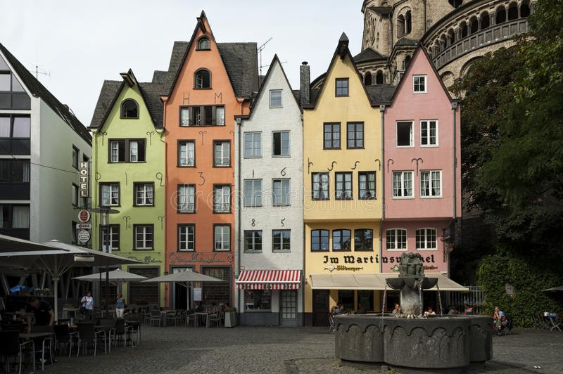 COLOGNE, GERMANY - SEPTEMBER 11, 2016: Colorful houses in Bavarian style and the Romanesque Catholic church `Gross Sankt Martin` stock photos
