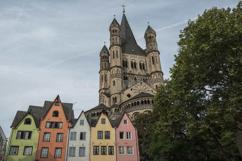 COLOGNE, GERMANY - SEPTEMBER 11, 2016: Colorful houses in Bavarian style and the Romanesque Catholic church `Gross Sankt Martin` royalty free stock photos