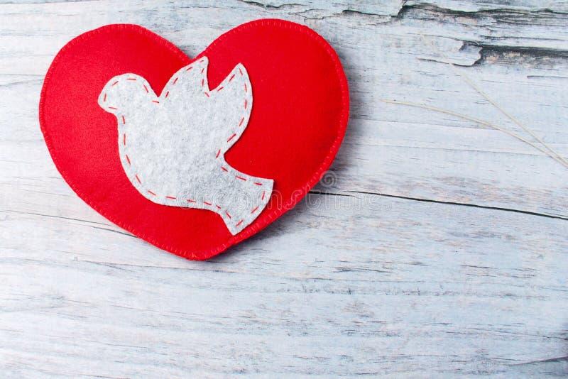 Colomba grigia ritenuta, cuore fatto a mano rosso su fondo di legno fotografia stock libera da diritti