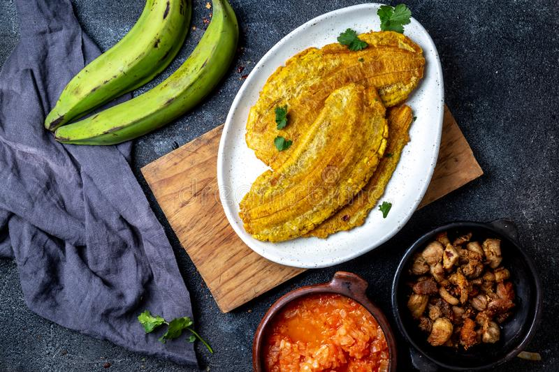 COLOMBIAN CARIBBEAN CENTRAL AMERICAN FOOD. Patacon or toston, fried and flattened whole green plantain banana on white royalty free stock photography
