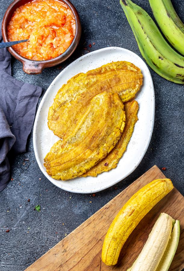 COLOMBIAN CARIBBEAN CENTRAL AMERICAN FOOD. Patacon or toston, fried and flattened whole green plantain banana on white stock photos