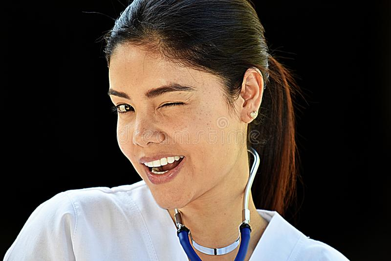 Colombian Female Nurse Winking Wearing Scrubs. A pretty young Colombian adult female royalty free stock photo