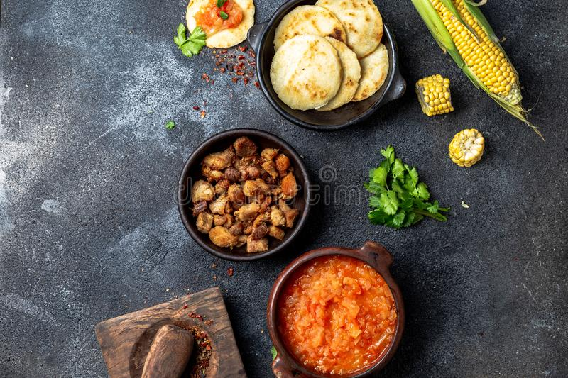 COLOMBIAN traditional food. Chicharron, maize arepas with tomato and onion sauce. Top view stock photo