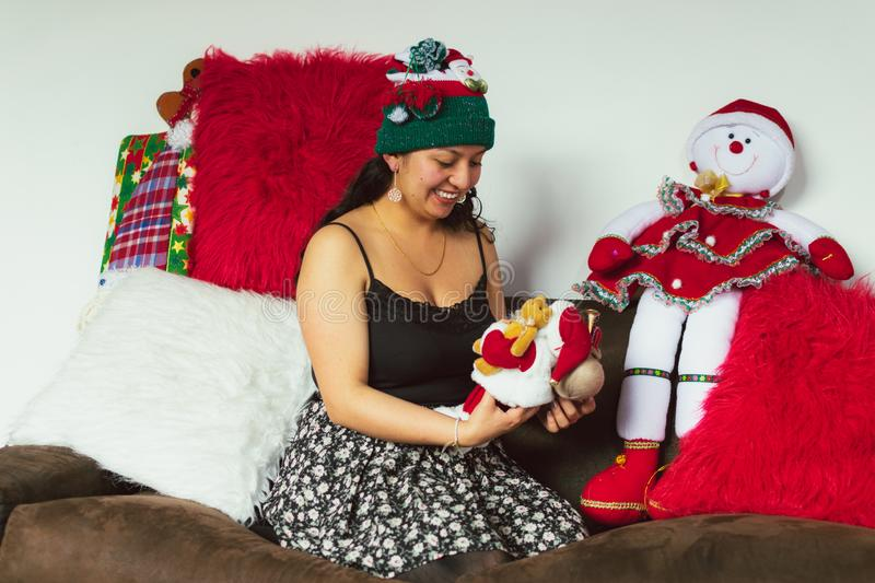 Colombian woman at Christmas sitting on the sofa with a Christmas doll in her hands stock images
