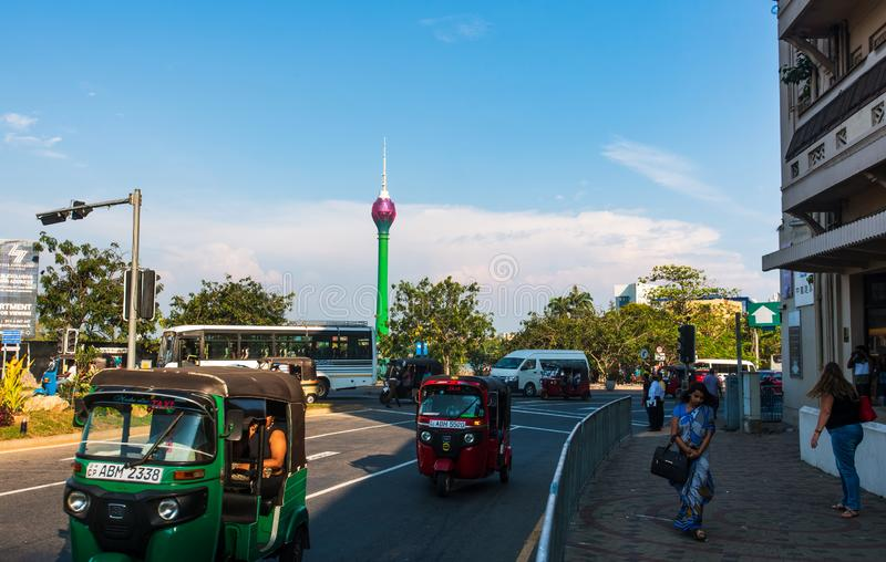 Colombo, Sri Lanka - April 5, 2019: Downtown Colombo street scene with Lotus tower in the background and tuk-tuk on the street. With people passing by royalty free stock images