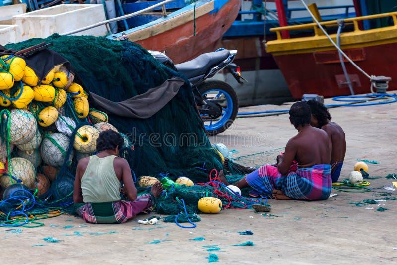 COLOMBO, SRI LANKA - 7 DICEMBRE 2013: I pescatori locali riparano le reti nello Sri Lanka fotografia stock libera da diritti
