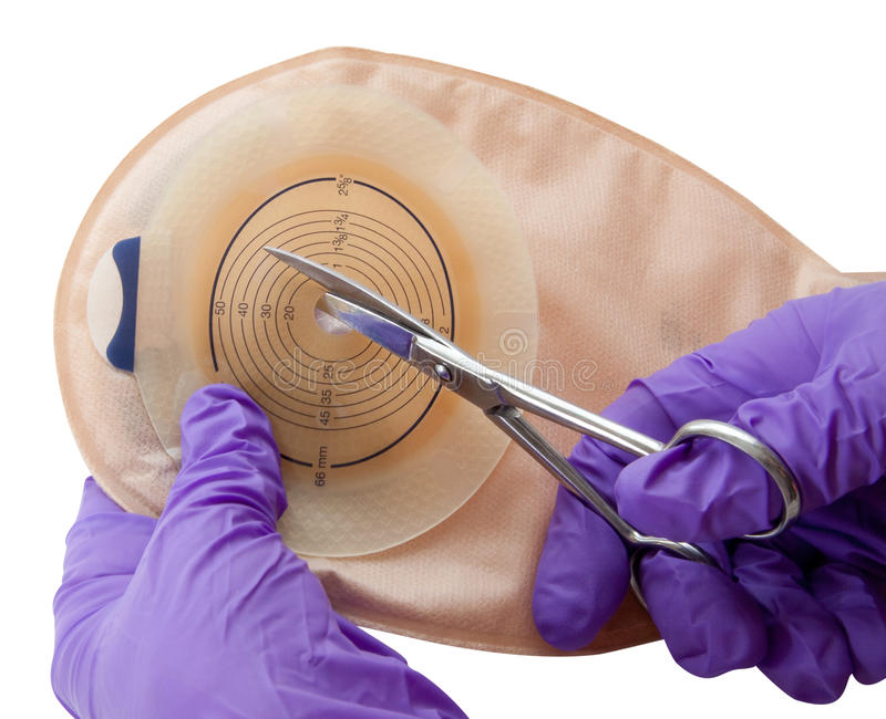 Colon cancer care. Using surgical gloves to cut a stoma pouch often used following a colostomy for colon cancer (isolated on a white background with clipping royalty free stock photos