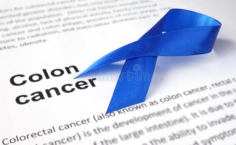 Colon cancer. Paper with colon cancer and dark blue ribbon royalty free stock image