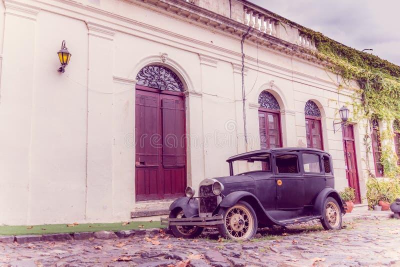COLONIA DEL SACRAMENTO, URUGUAI - 4 DE MAIO DE 2016: o carro velho rústico estacionou na rua ao lado de uma casa antiga fotos de stock royalty free