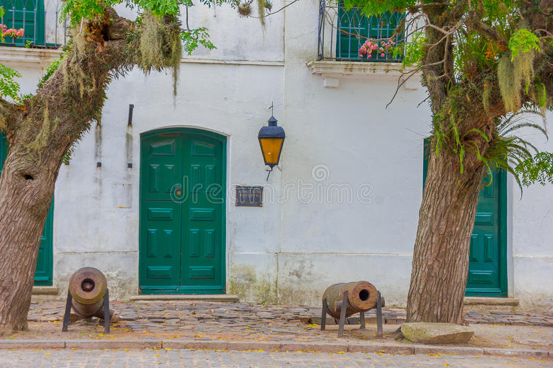 COLONIA DEL SACRAMENTO, URUGUAY - MAY 04, 2016: nice ancient ehite house with green doors and windows, two big trees in stock image