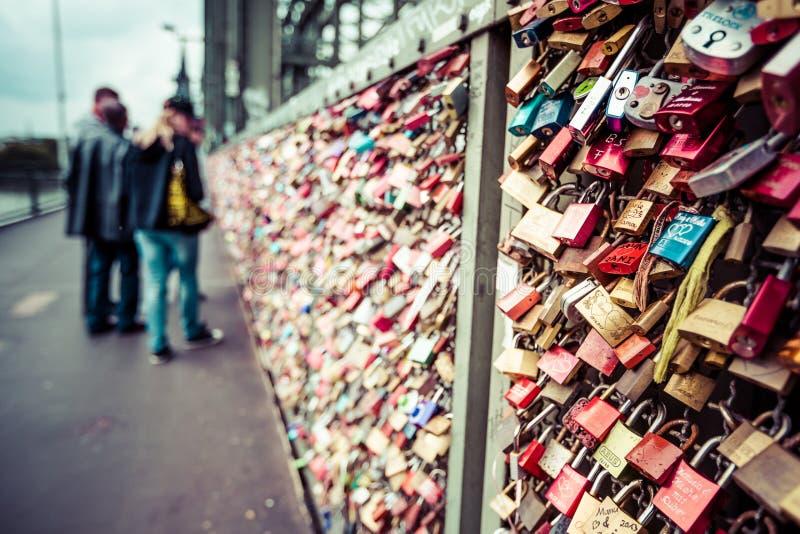 COLONIA, GERMANIA - 26 agosto 2014, migliaia di serrature di amore che gli innamorati chiudono al ponte di Hohenzollern per simbo fotografie stock