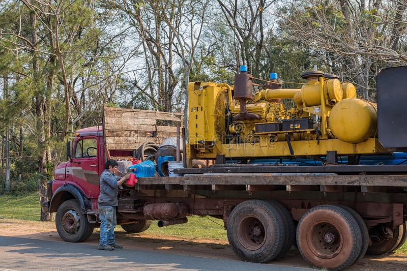 Old truck as it is typical for Paraguay. On the loading platform a machine for drilling deep wells. Colonia Independencia, Paraguay - August 30, 2018: Old truck royalty free stock image