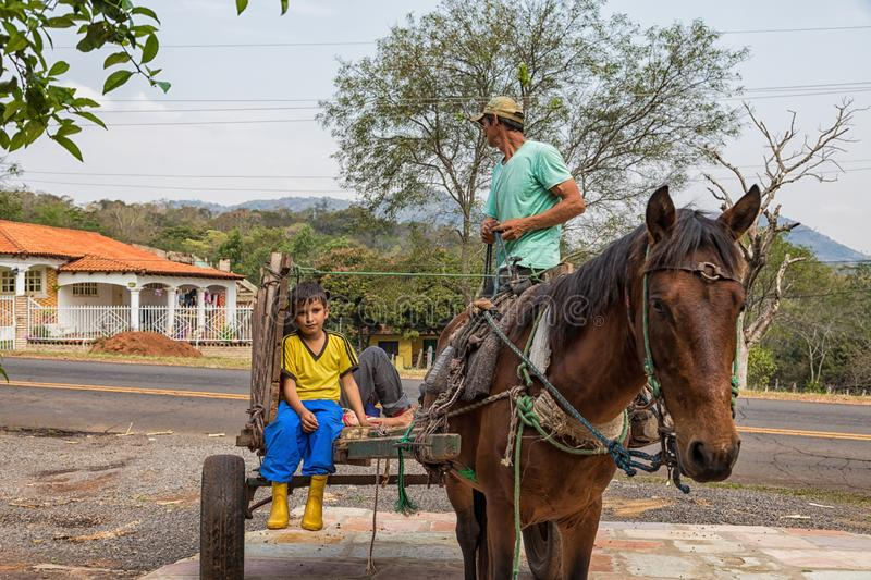 Poor indigenous family in Paraguay with uniaxial carriage and horse. stock photo