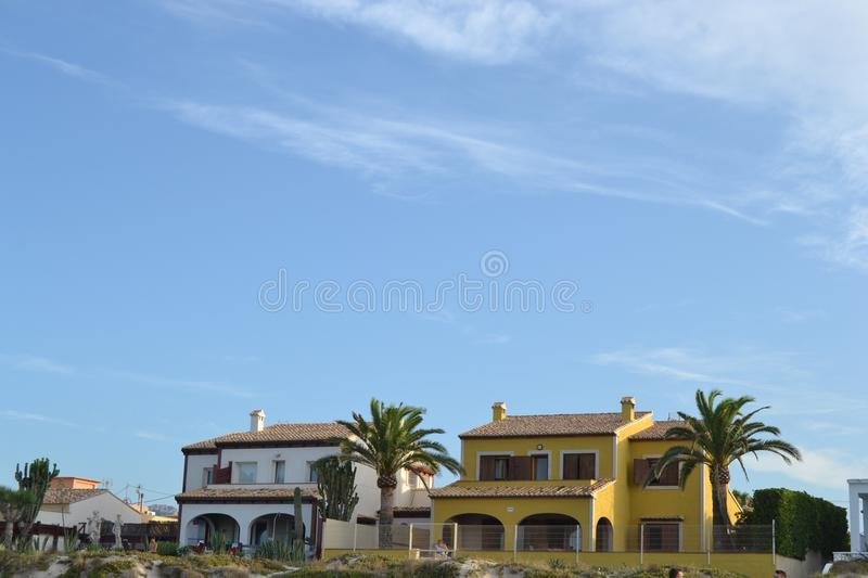 Colonial beach houses. In bright yellow and white in the Spanish coast stock photography