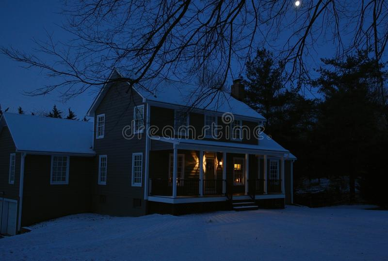 Colonial house at night with snow covered ground and moon shinning above tree limbs. On cold winter morning stock photo