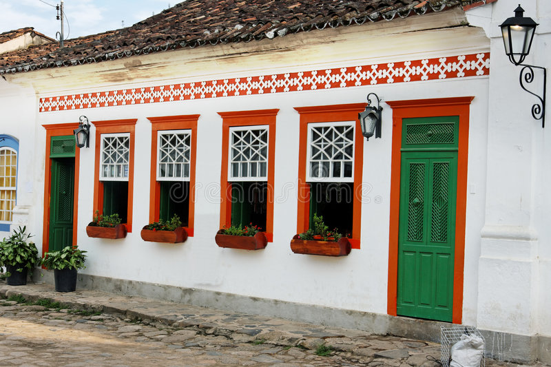 Colonial House Paraty Rio de Janeiro Brazil. A typical colorful red, white and green colonial house facade with wood doors and windows, iron street lamps at a royalty free stock photos
