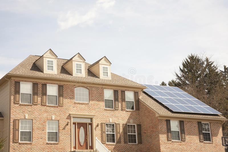 Colonial house with solar panel. Brick colonial home with solar panels on the roof royalty free stock images