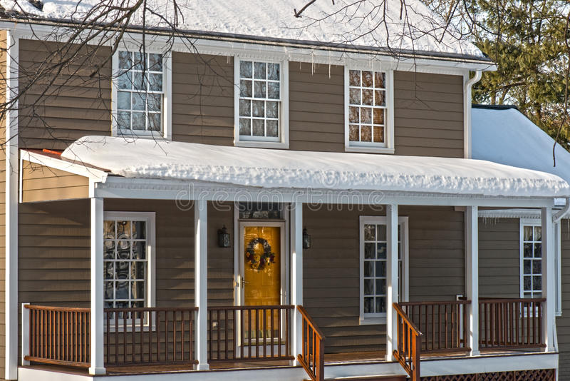 Colonial house in Winter. Attractive house from Colonial period seen on a snowy Winter day, constructed of clapboard with veranda outside the front door with royalty free stock photos