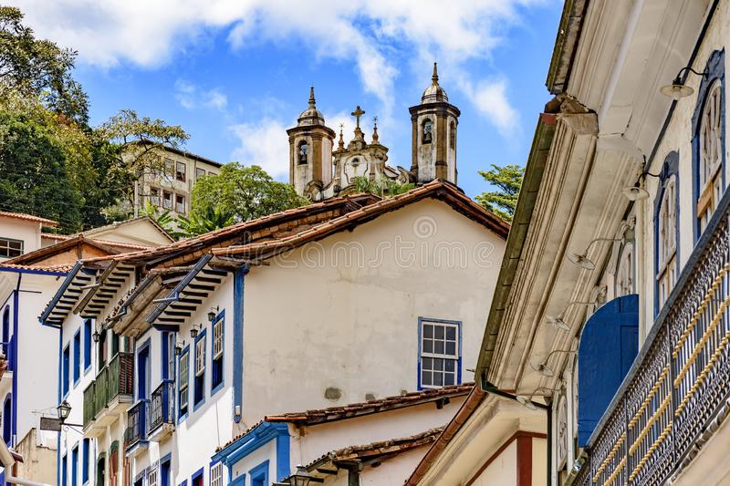 Colonial houses of the center of the historic Ouro Preto city. In Minas Gerais, Brazil with its famous churches and old buildings in background stock photo