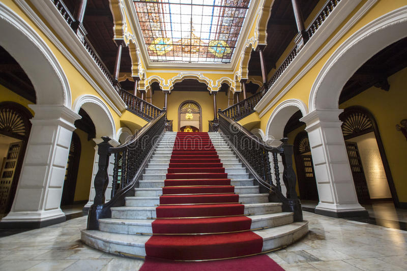 Colonial staircase at Archbishop's Palace in Lima, Peru. Yellow colonial interior and marble staircase with red carpet at Archbishop's Palace in Lima during the royalty free stock images