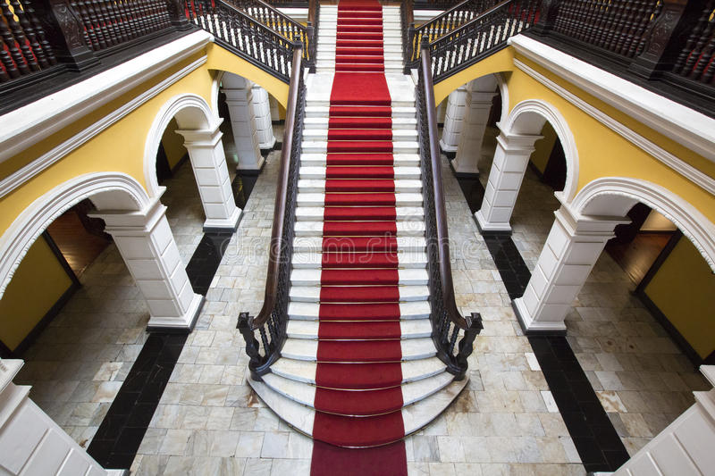 Colonial staircase at Archbishop's Palace in Lima, Peru. Yellow colonial interior and marble staircase with red carpet at Archbishop's Palace in Lima during the royalty free stock photos