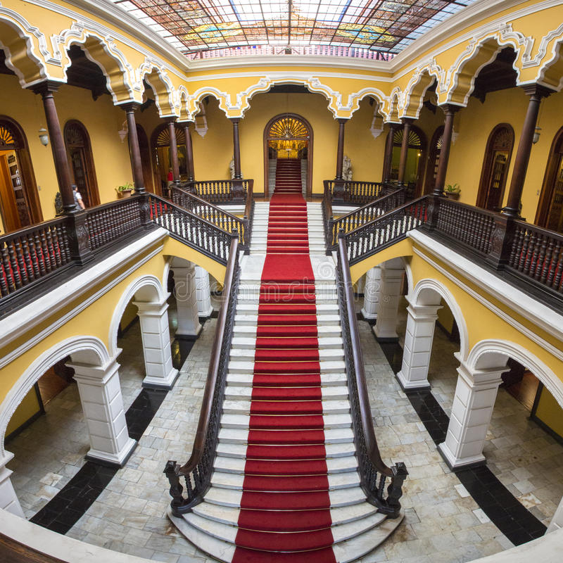 Colonial staircase at Archbishop's Palace in Lima, Peru. Yellow colonial interior and marble staircase with red carpet at Archbishop's Palace in Lima during the stock photo