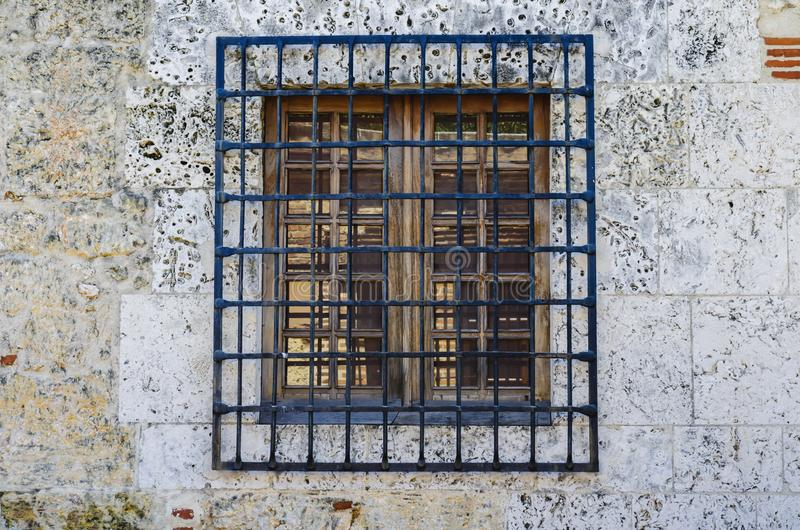 Colonial window with iron bars with limestone wall. Is typical of the houses in the colonial area of Santo Domingo stock photo