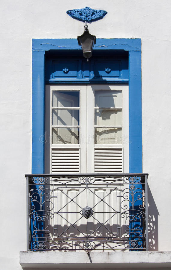 Colonial Window Sao Joao del Rey. Detail of a typical colonial house with a blue wood window with a small iron fence balcony in Sao Joao del Rey, Minas Gerais royalty free stock photos