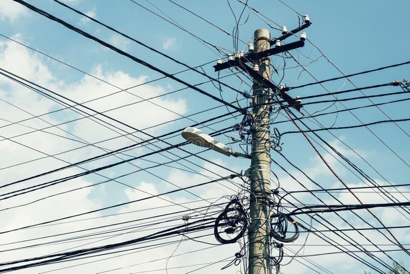Colonna con i lotti dei cavi e di una lampada di via sul backgroun del cielo fotografia stock libera da diritti