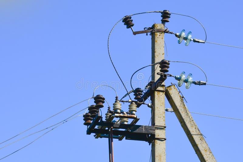 Colonna della linea di trasmissione di elettricit? con gli isolanti trasparenti Primo piano fotografato Contro il cielo blu immagini stock