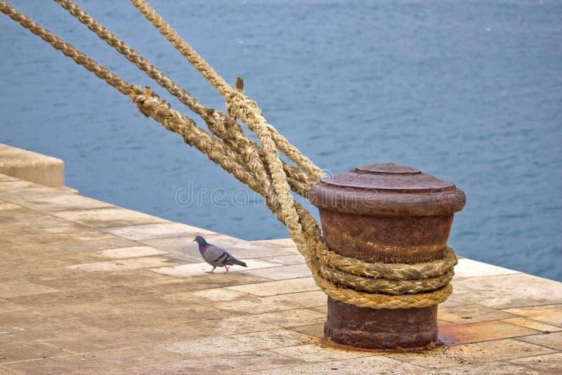 Colonna di ormeggio arrugginita di attracco con le corde della nave immagini stock