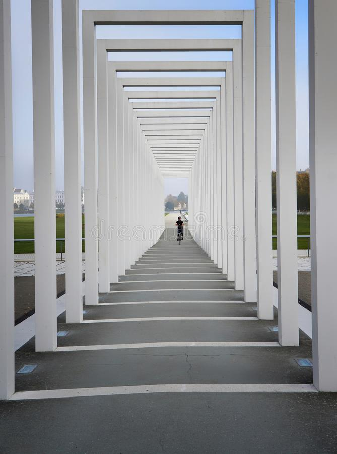 Colonnades with unicyclist in the background. Entrance to the floating meadow in Schwerin. Germany. Architecture, burgsee, lake, fog, lantern, pillar, tourism royalty free stock photos