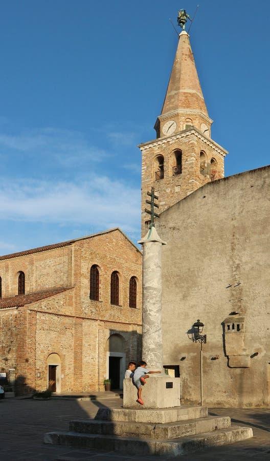 Colonne monumentale de Grado, avec des enfants jouant là-dessus, dans l'avant à la cathédrale antique de Santa Eufemia photographie stock