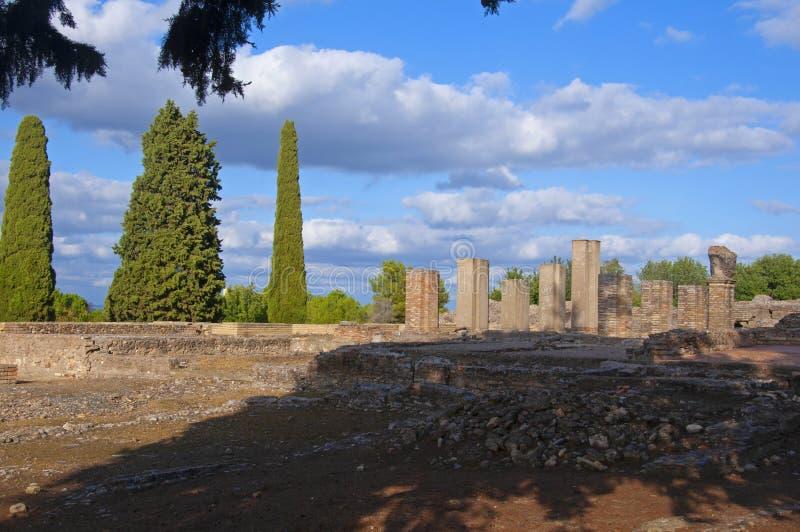 Colonne rosse di antico marrone chiaro, rovine nella piazza romana, cipressi e cielo azzurro con nuvole bianche immagine stock