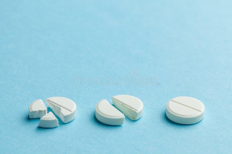 Colonnes blanches sur fond bleu. Peu de pilules cassées en deux, réduisant la dose du médicament. Espace de copie pour le texte photos libres de droits
