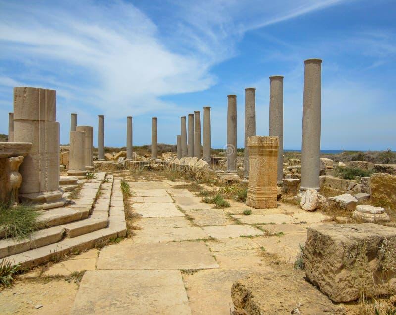 Colonnes contre le ciel bleu avec les nuages effilés blancs aux ruines romaines antiques de Leptis Magna en Libye images libres de droits