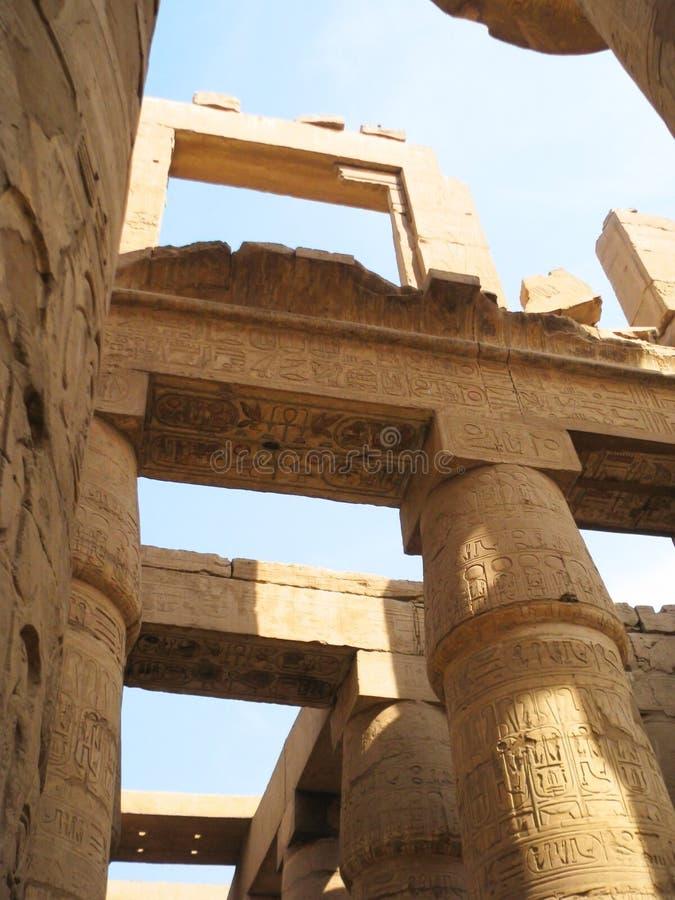 Colonnes en pierre et faisceaux décorés des hiéroglyphes en Egypte images libres de droits