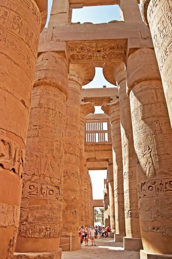 Colonnes proches de touristes non identifiées du grand Hall hypostyle aux temples de Karnak, Egypte images stock