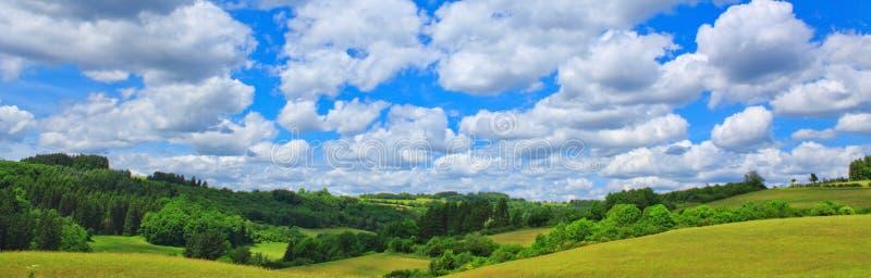 Coloque com grama verde e o céu azul com nuvens fotografia de stock royalty free